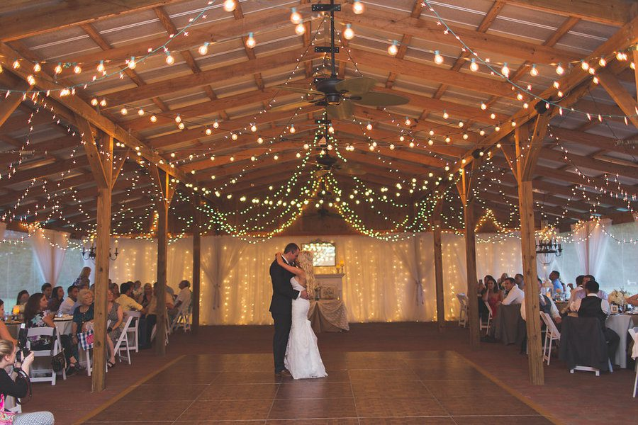 barn wedding lights. First Dance Together Under The Strung Lights Of Stable. Barn Wedding