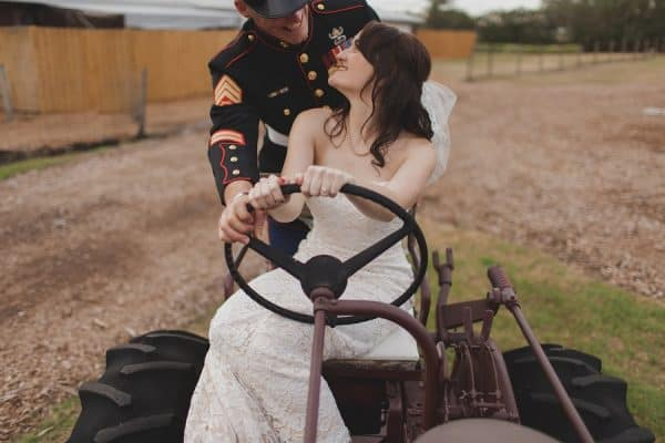 Groom in uniform and bride in lace play on a rustic tractor on their wedding day at Cross Creek Ranch