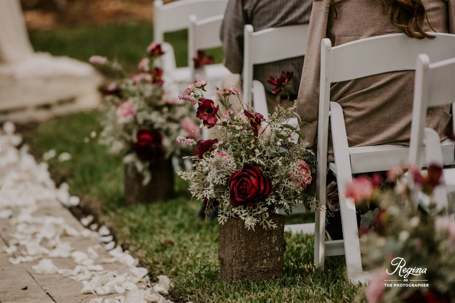 Wooden stumps with fall flower arrangements lining the ceremony aisle