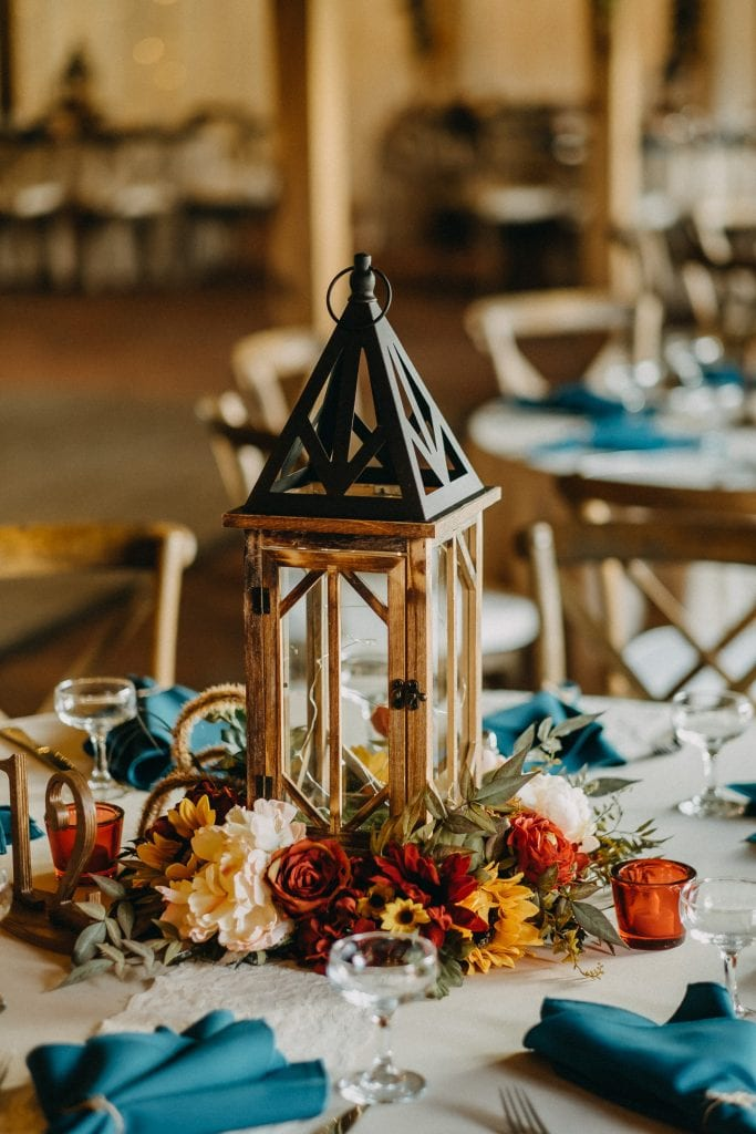 Wooden lanterns and fall flowers for an Autumn wedding centerpiece