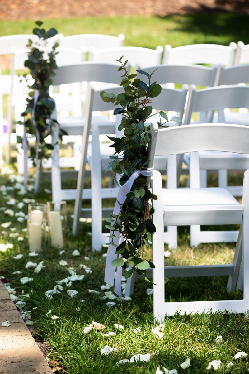 The white garden chairs decorated for Isabela and Zach's wedding ceremony
