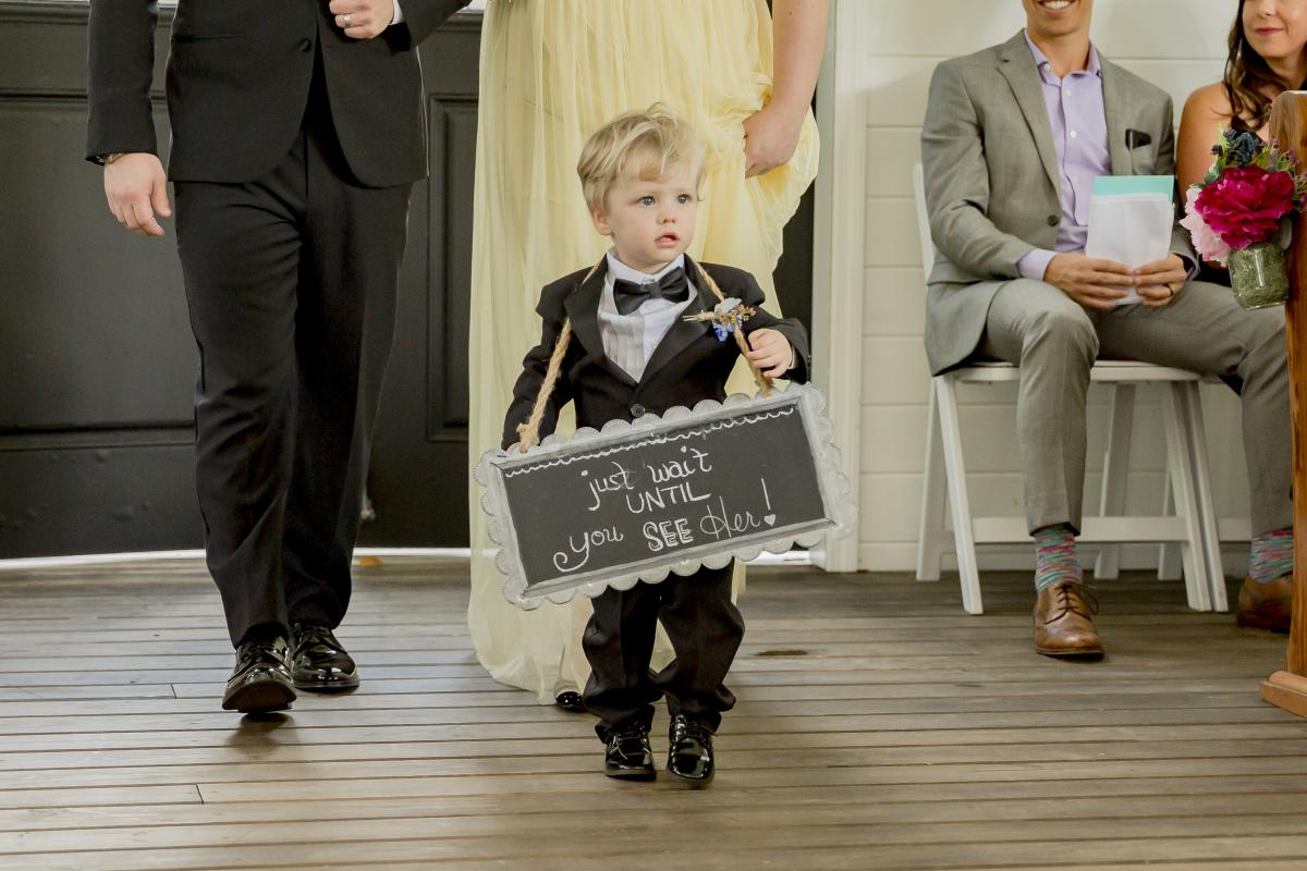 """Ring bearer walking down the aisle with a sign that reads """"just wait until you see her"""""""