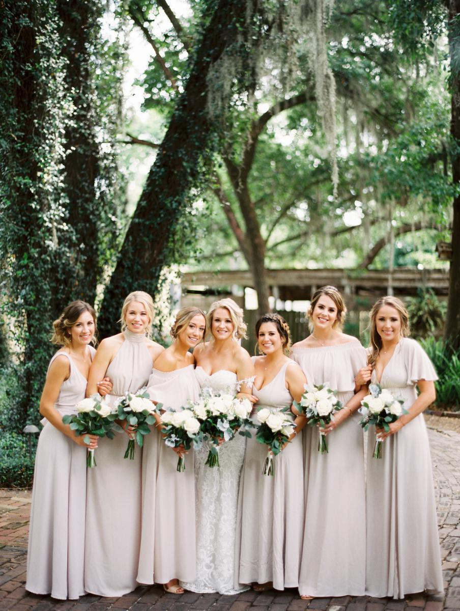 Krista and her bridesmaids who are dressed in light beige bridesmaid dresses