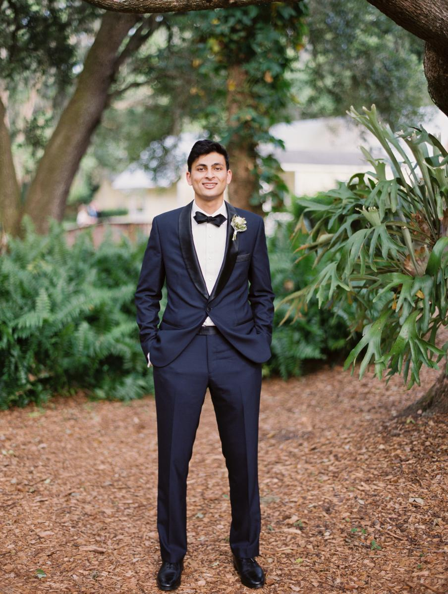 Ricky dressed in a classic all black wedding suit with black bowtie