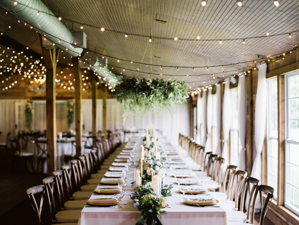 Krista and Ricky's long banquet style tables with greenery garlands and hanging greenery chandeliers