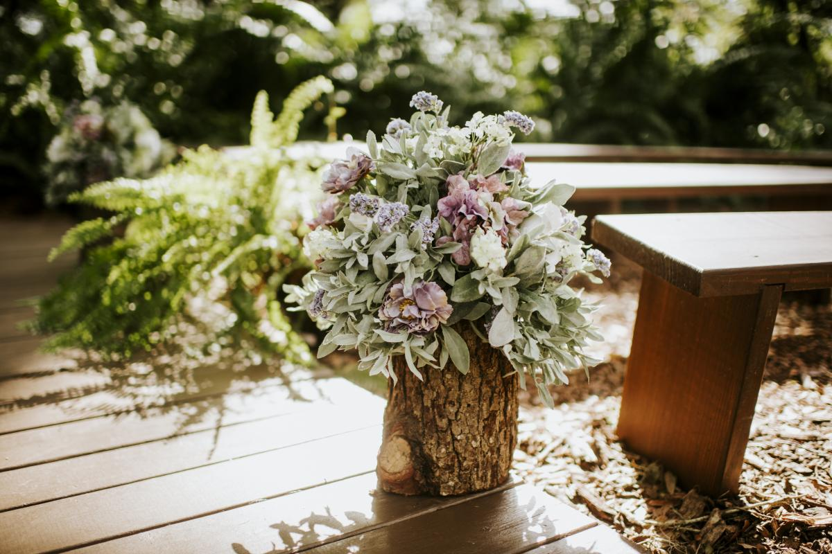 Wooden stumps with large floral and greenery arrangements on top