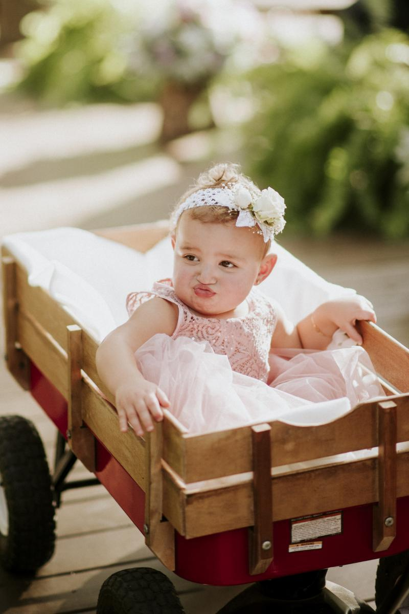 The flower girl is being walked down the aisle in the little red wagon