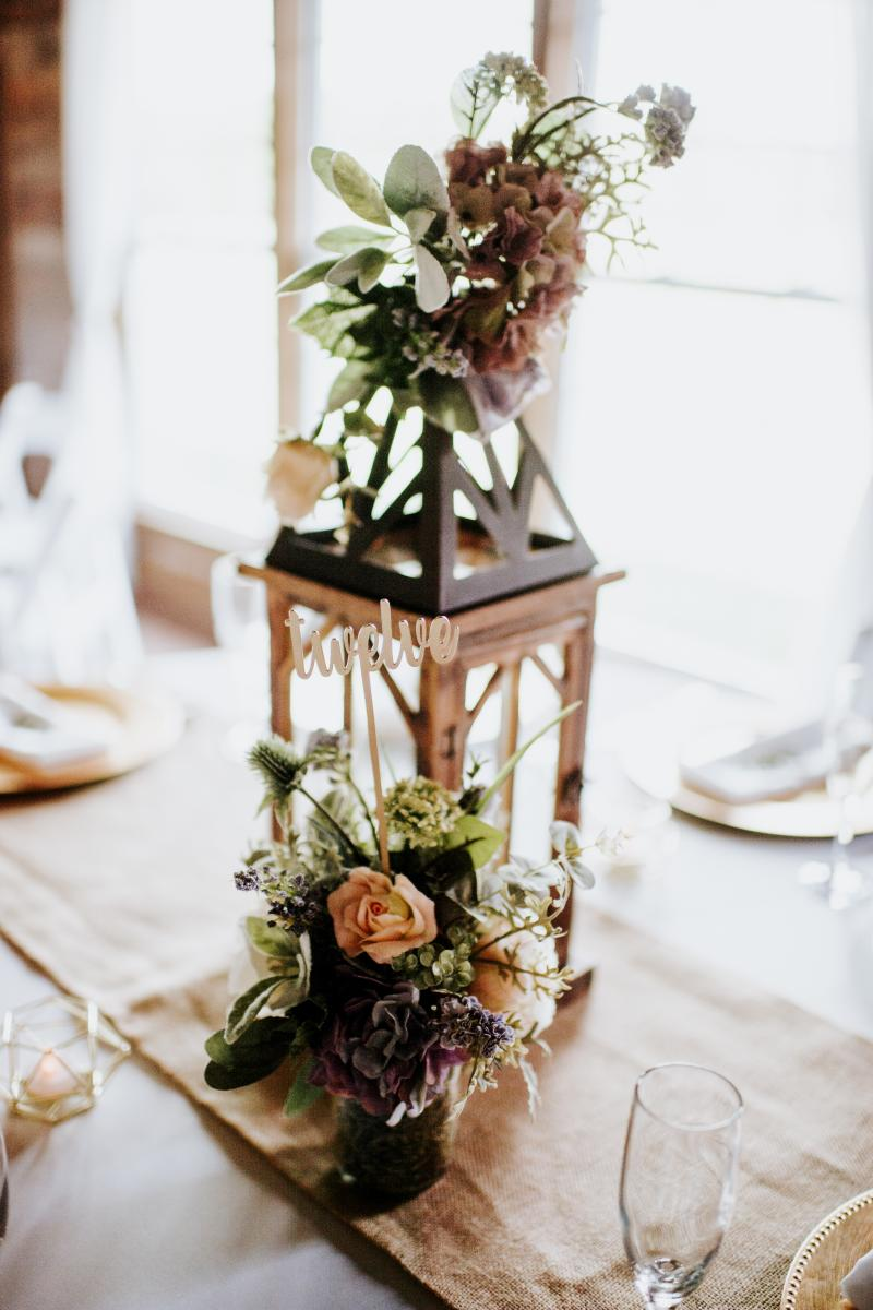 Wooden lanterns decorated their reception tables with small bouquets of flowers