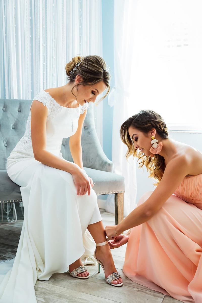 Andreina's Maid of honor helping her with her shoes