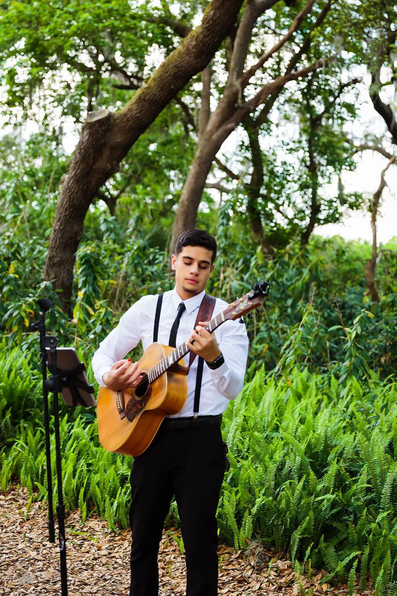 Jariah Higgins playing acoustic guitar during the ceremony