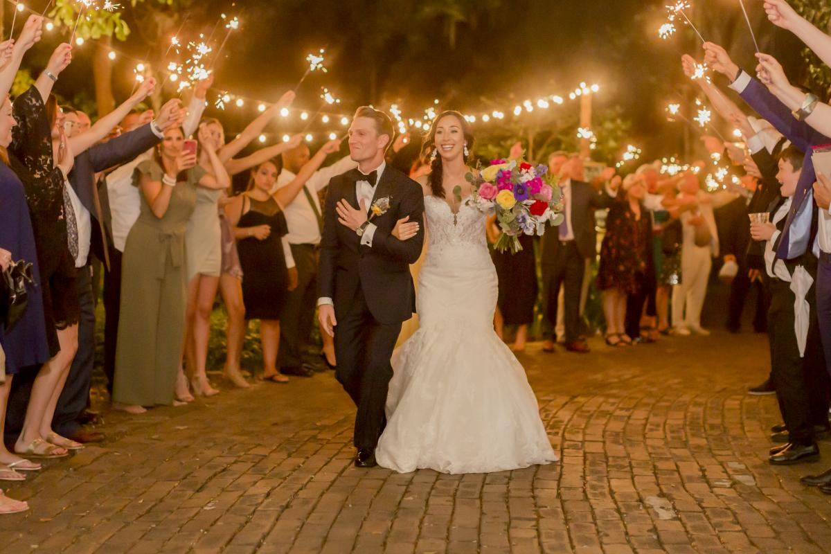 Alexa and Steven walking through a tunnel of sparklers