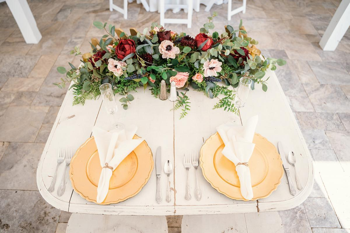 Elegant wedding sweetheart table with gold chargers