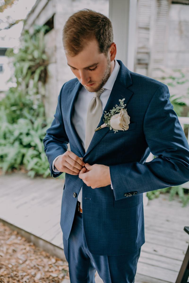 Matt getting dressed in his navy blue grooms suit