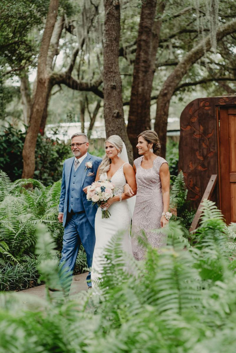 Brandy and her parents walking down the aisle in the Enchanted Forest