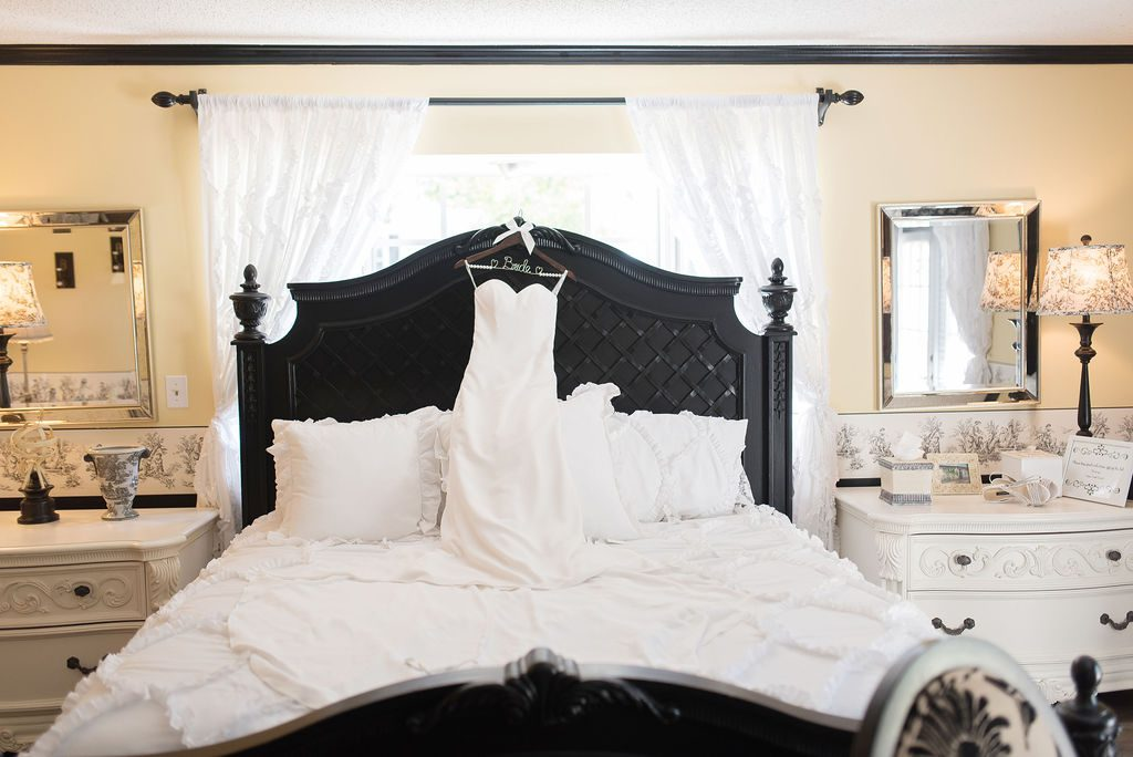 The bride's dress hanging on the French Country Inn bed