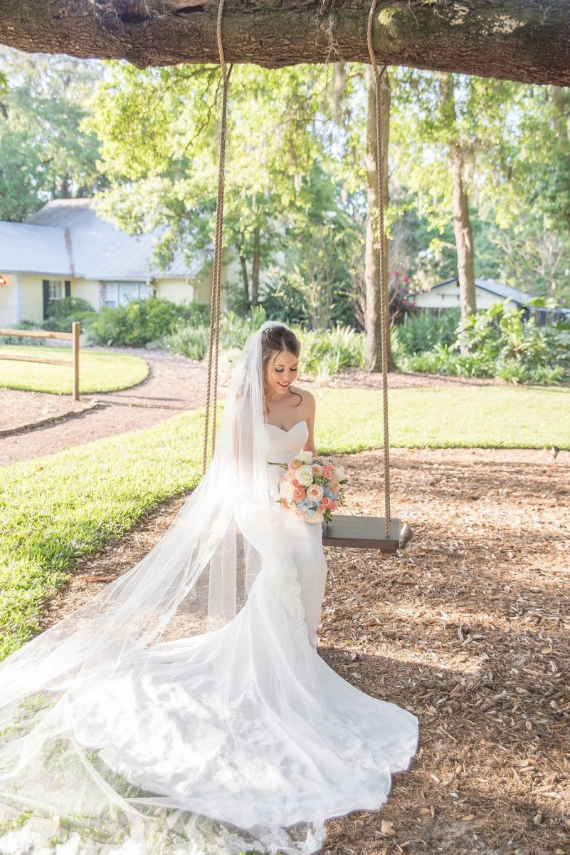 Kathleen in her bridal attire sitting on the bridal swing