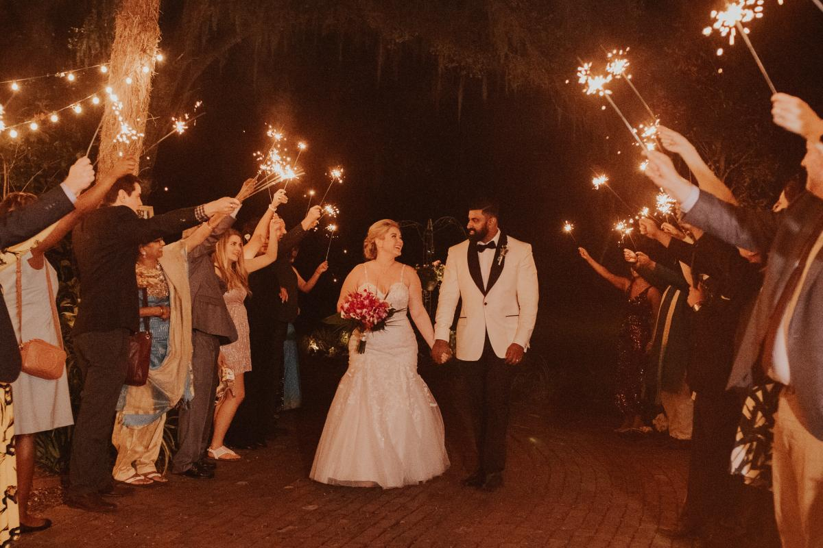 Sadie and Kiran walking through sparklers for their grand exit