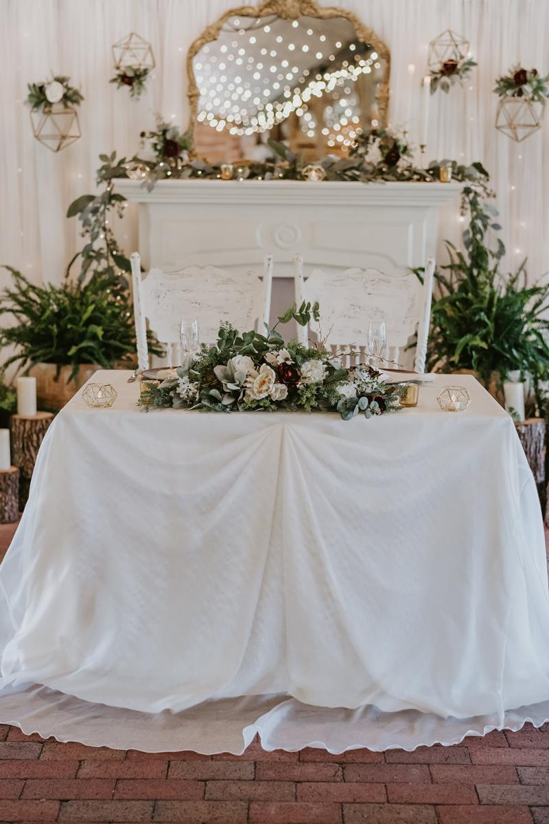 Kirstin and Julian's sweetheart table with wooden stumps, large ferns and candles