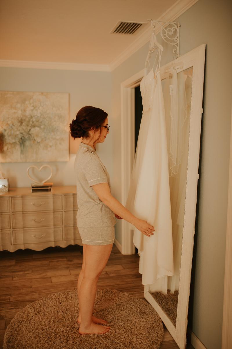 Liz looking at her stunning wedding dress