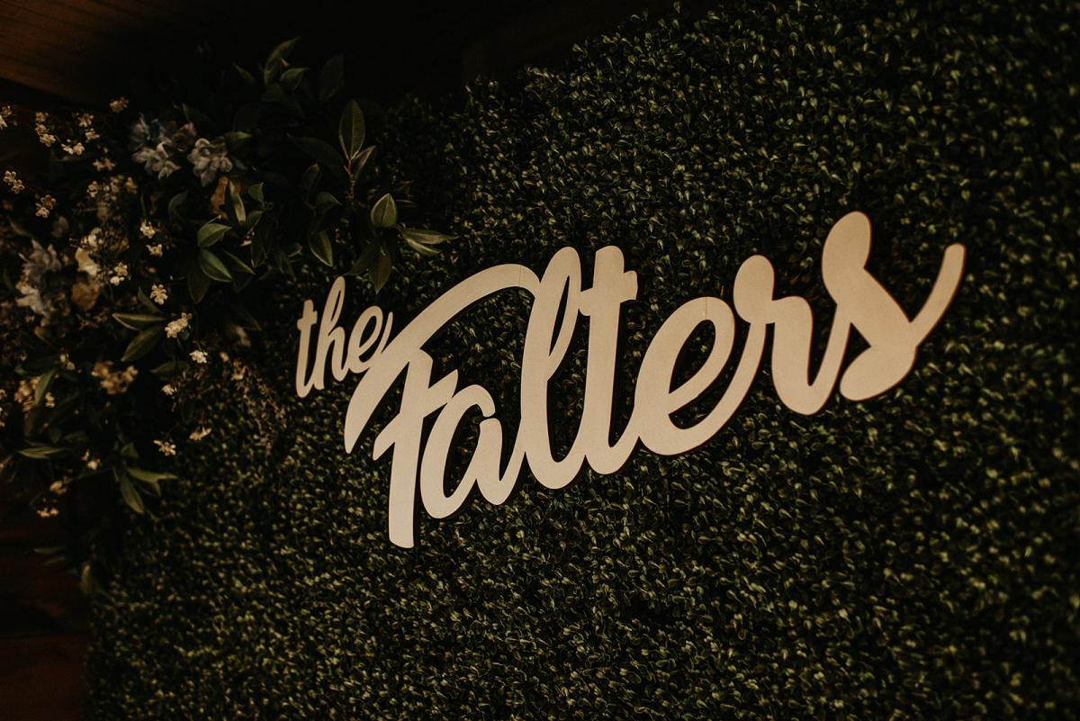 The Falters name written in gold on the green wall for their photo booth