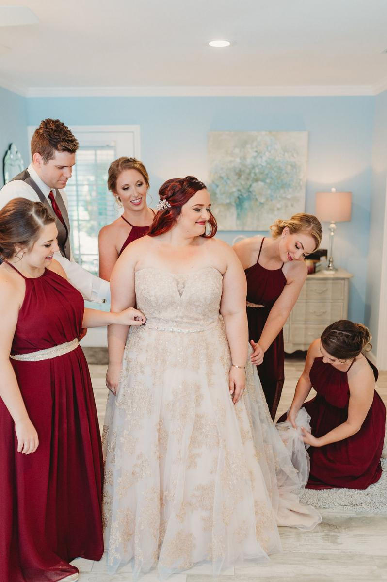 Heather's bridal party helping her get her dress on