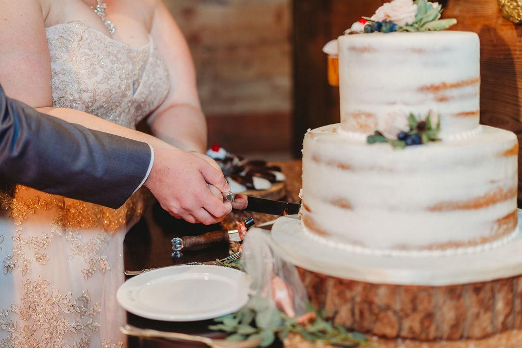 Heather and Jarrod cutting their rustic modern wedding cake