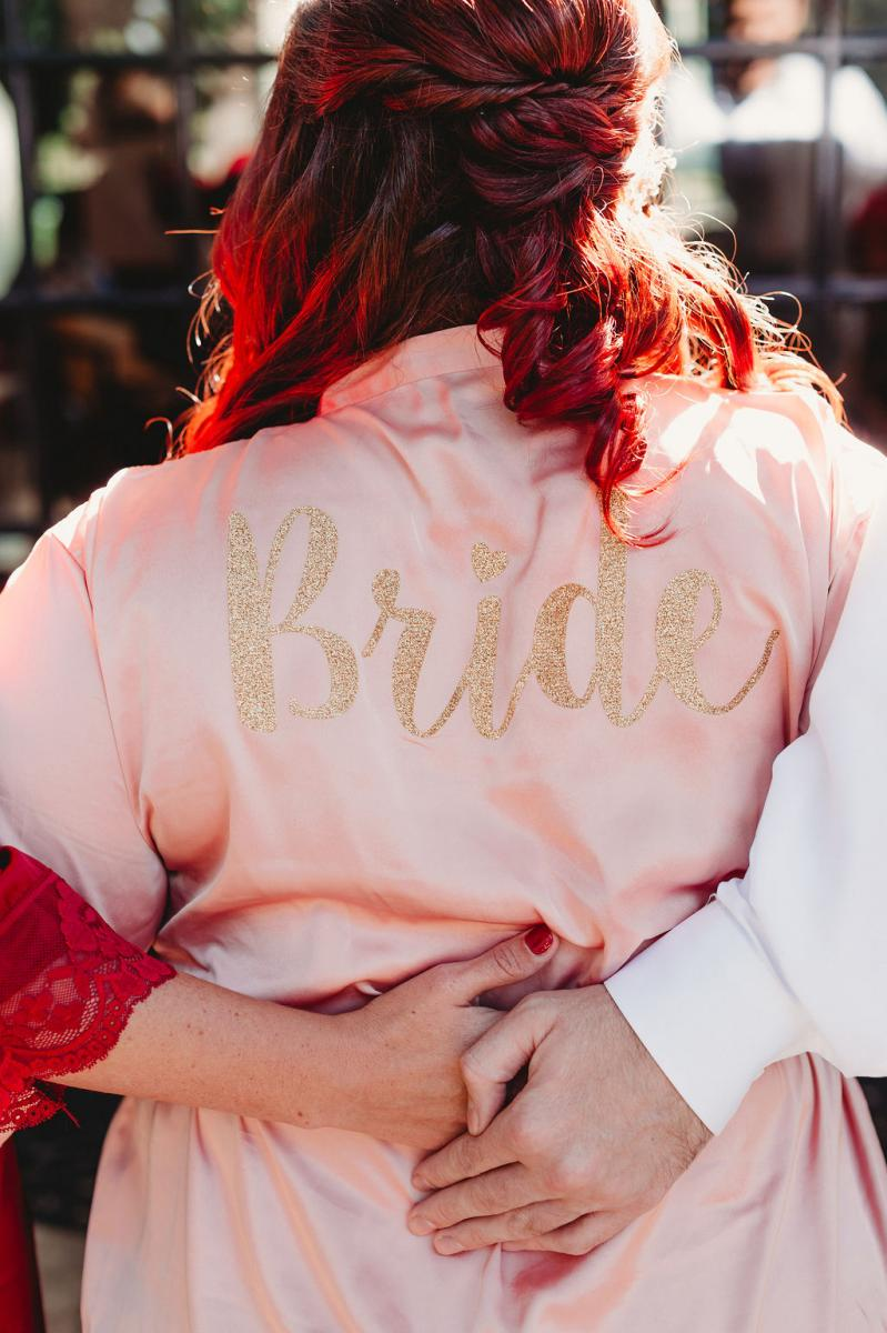 Heather wore a pink robe with the word Bride written on the back in gold glitter letters