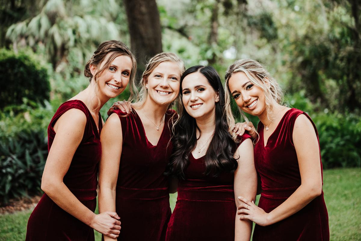 Nina's bridesmaids wearing dark burgundy