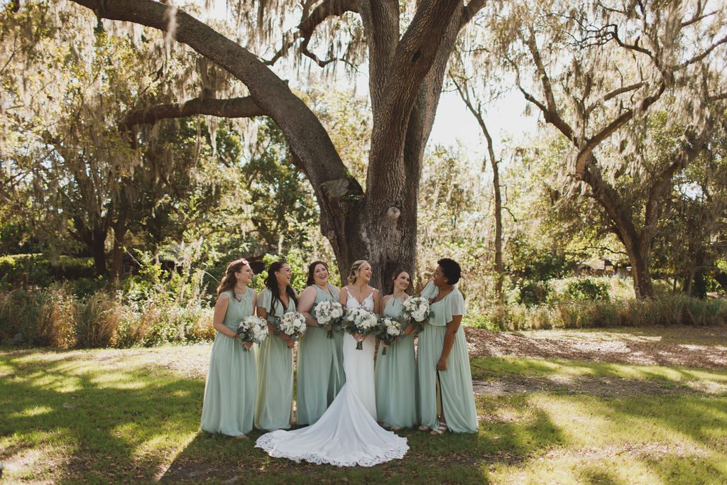 Megan's bridesmaid's dressed in long muted sage green gowns.