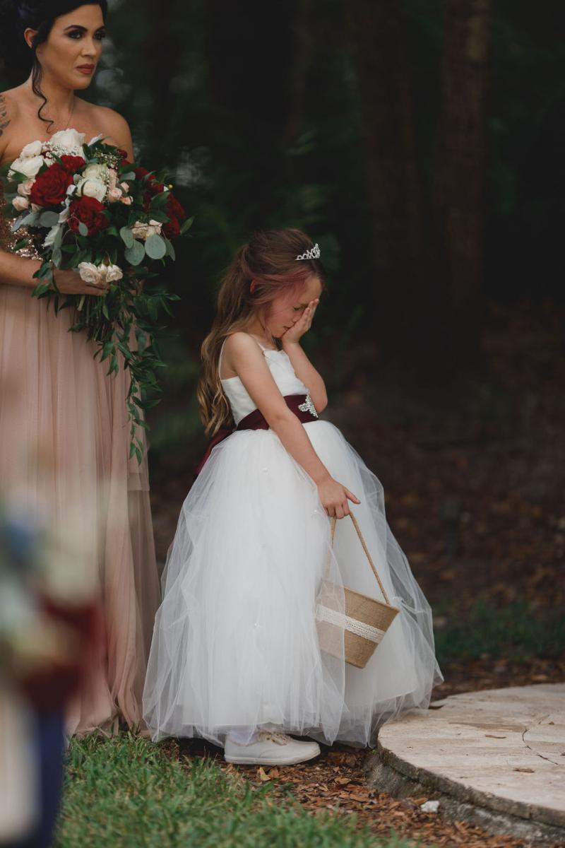 The adorable flower girl in a white dress with burgundy belt