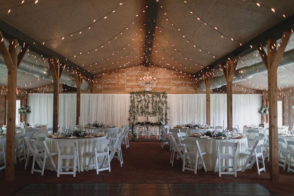 Barn wedding reception with lots of greenery