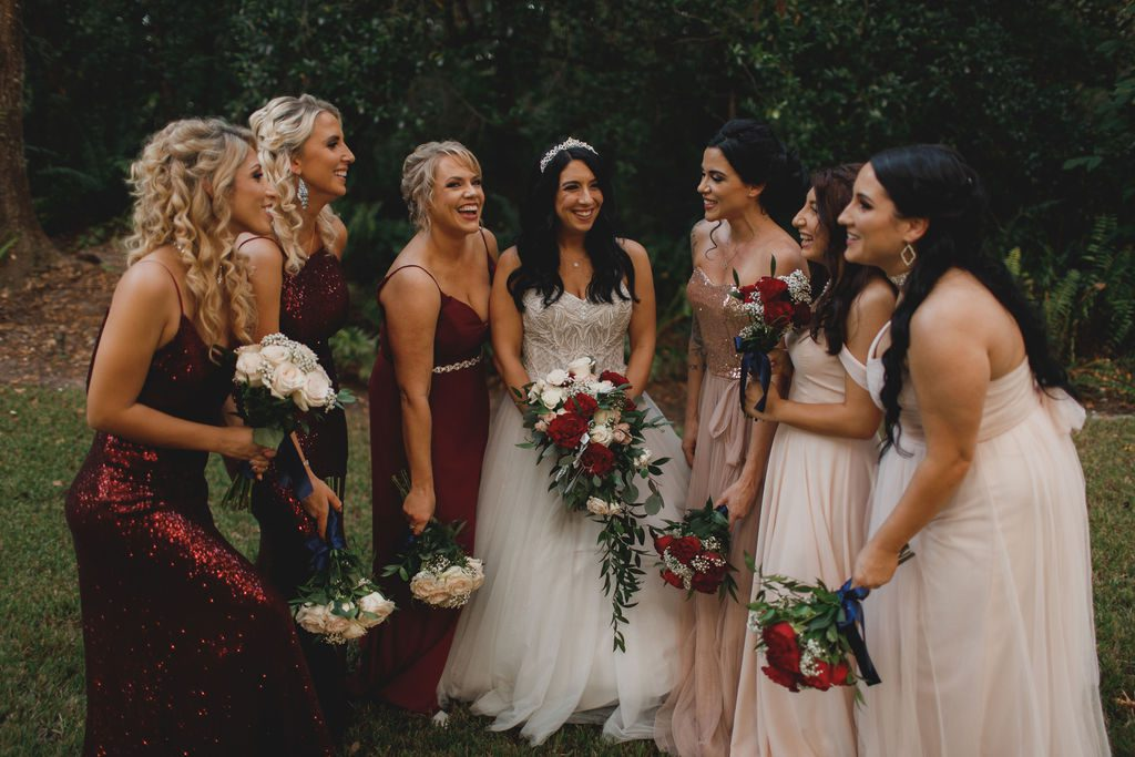 Jennifer and her bridesmaids in mismatched burgundy and blush dresses