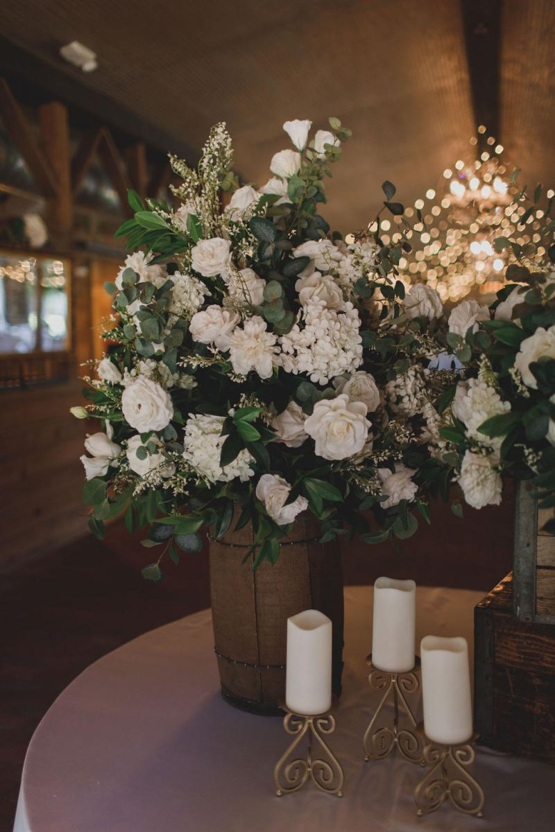 The entrance table centerpieces filled with lots of greenery and white flowers. So elegant