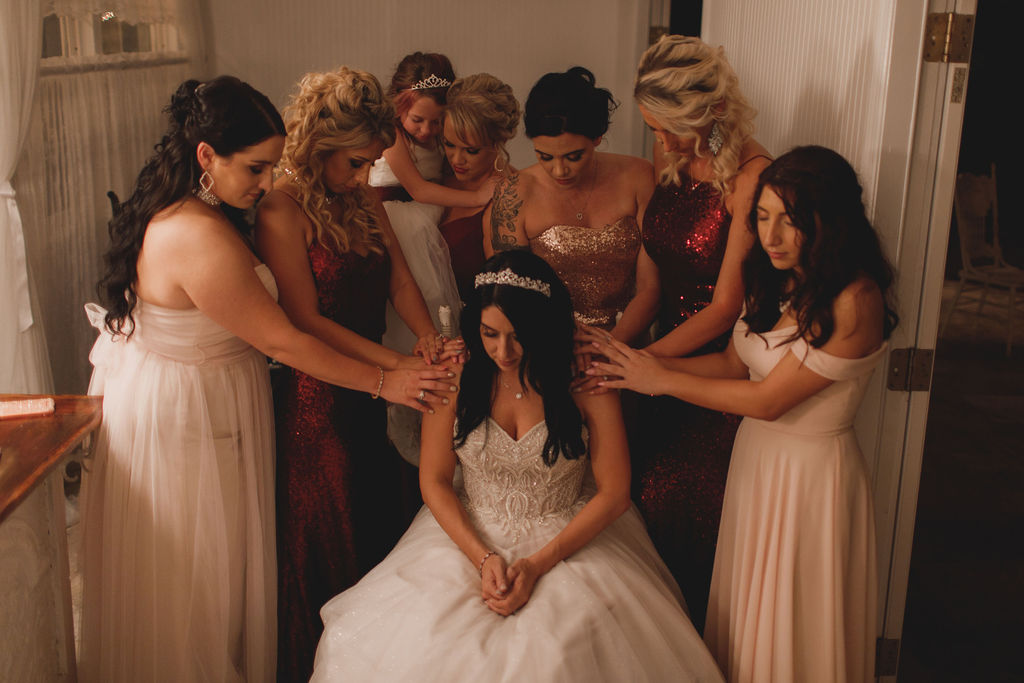 A prayer with the bride and her bridal party
