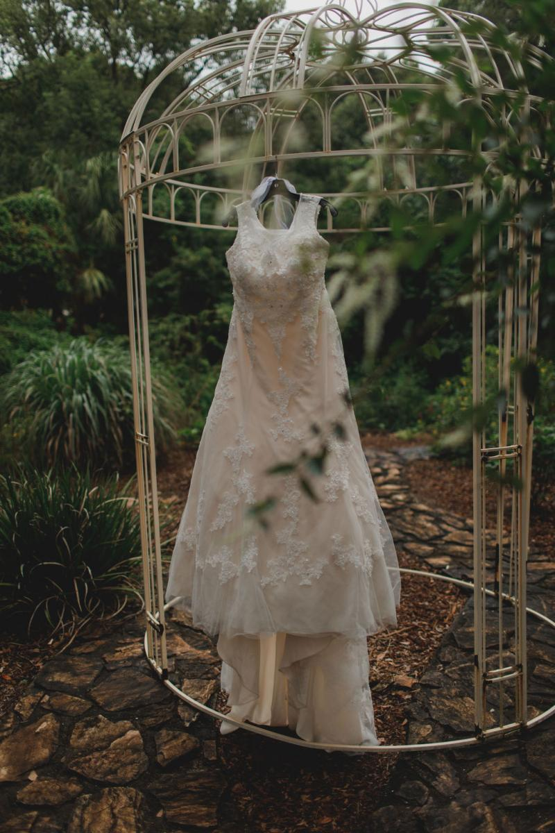 Tori's wedding dress hanging in the butterfly garden