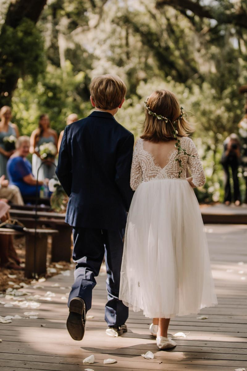 The ring bearer and flower girl walking down the ceremony aisle