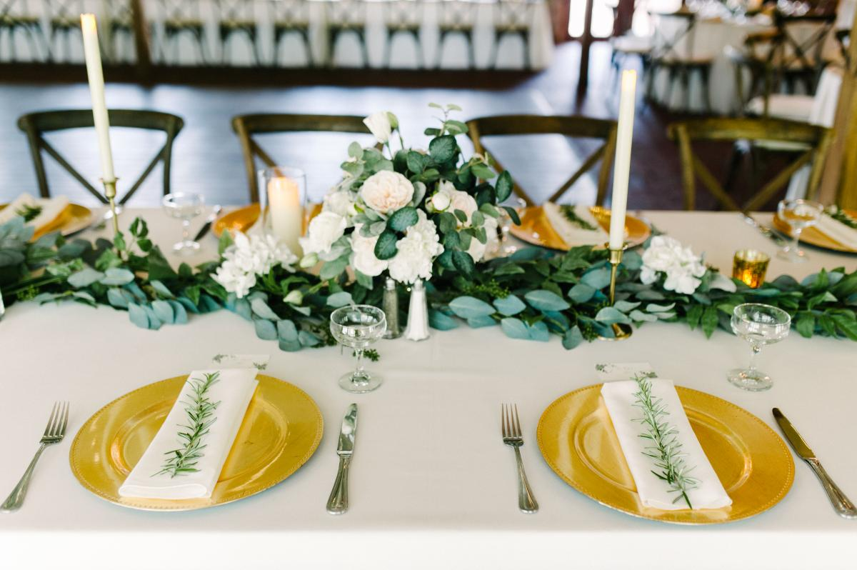 Long garlands of greenery with small bouquets of white roses filled the guests tables