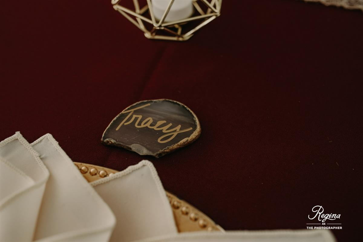 Stone place cards with guests names written in gold calligraphy