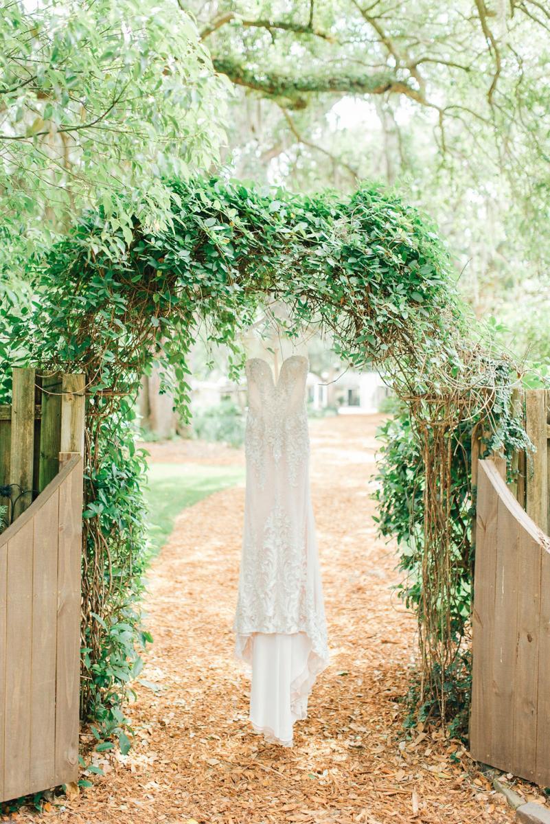 Sinnikka's wedding dress hanging from a greenery arch