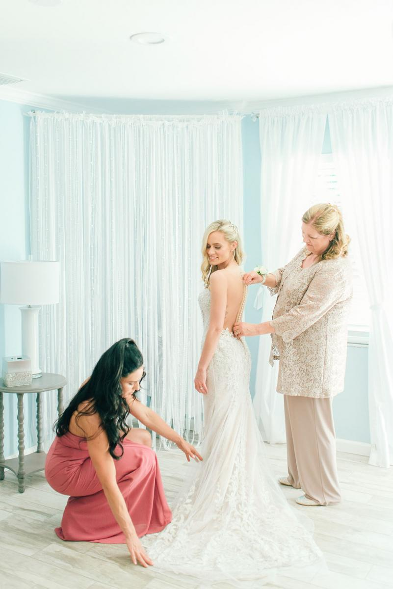 Sinnikka getting her dress on with the help of her mother and sister