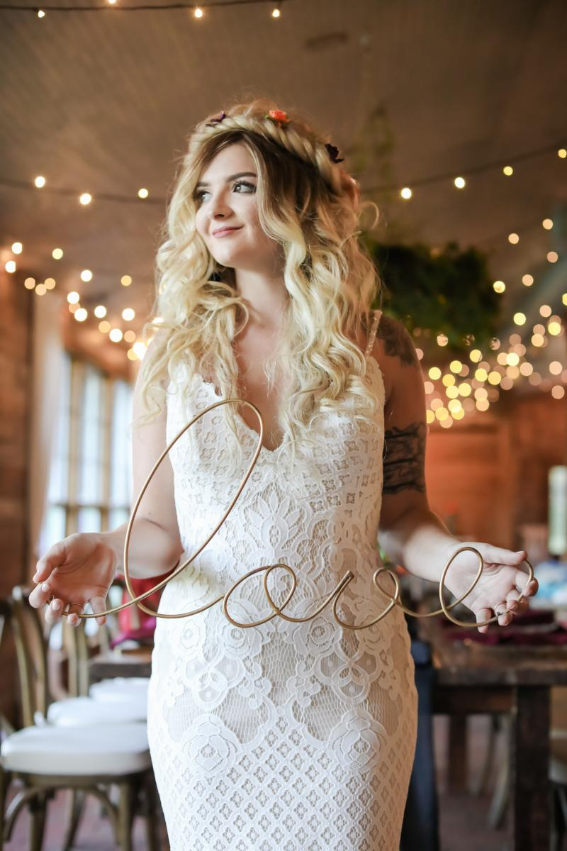Model wearing a boho dress and holding a gold wire love sign