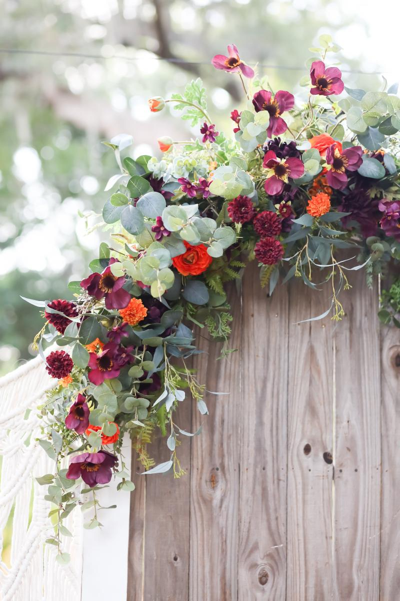 Floral spray on top of the door for the moody boho ceremony backdrop