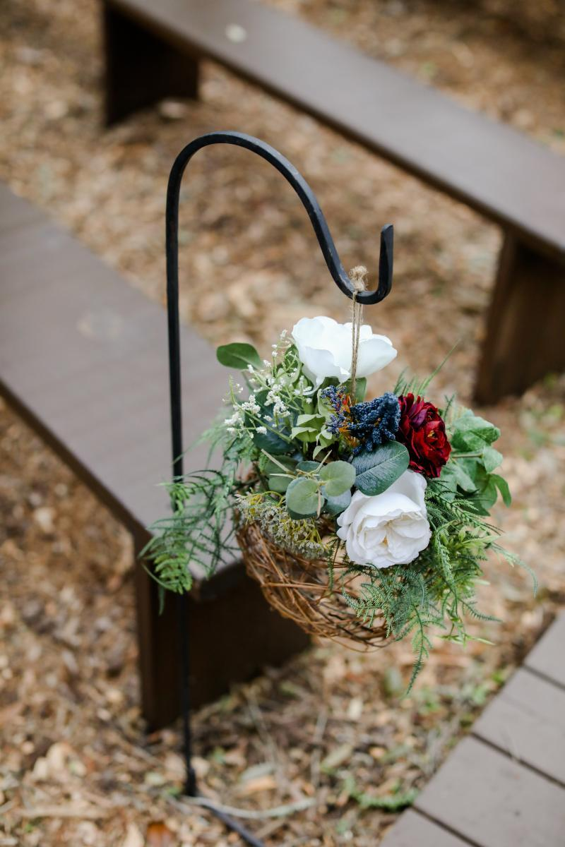 Grapevine wreath balls topped with greenery and flowers hang on shepherd hooks