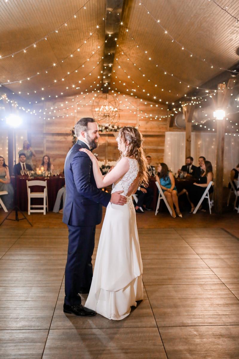 First dance underneath twinkle lights inside our Florida barn wedding venue