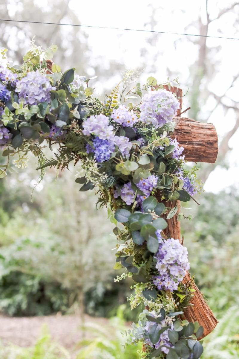 Purple wedding flowers on a rustic wood arch