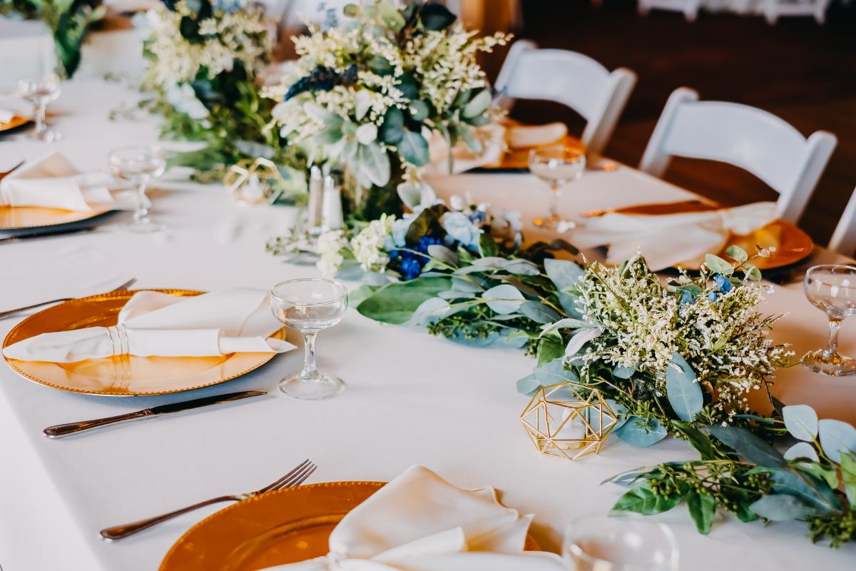 Garlands of greenery and gold chargers for this greenery filled wedding