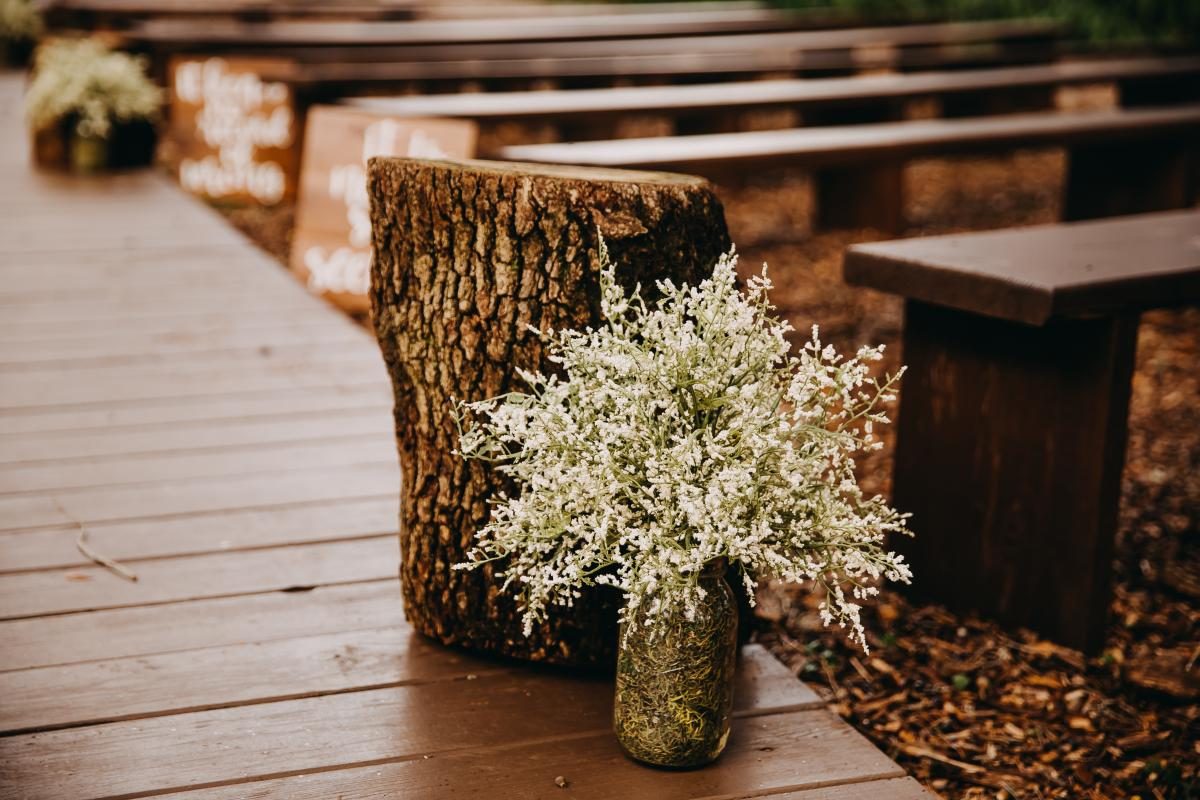 Wooden stumps and mason jars filled with while flowers line the aisle at the ceremony site