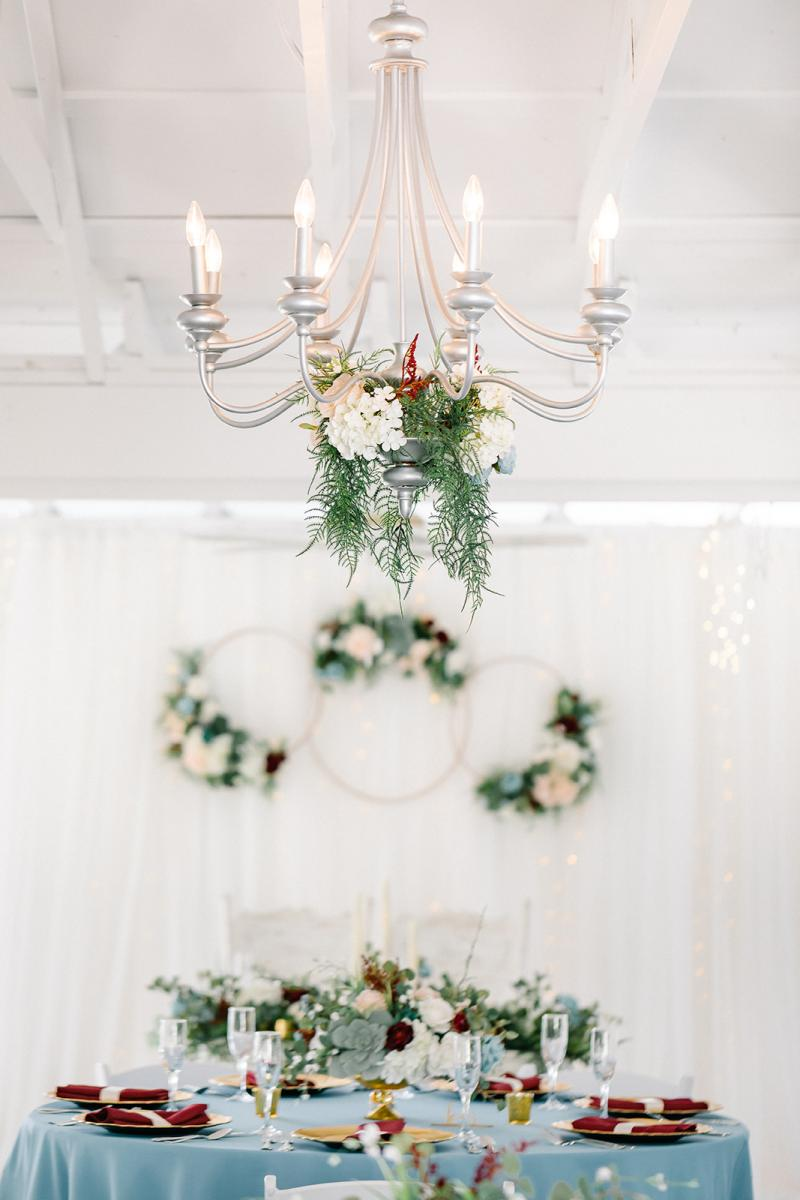 The chandeliers are dripping in greenery and flowers