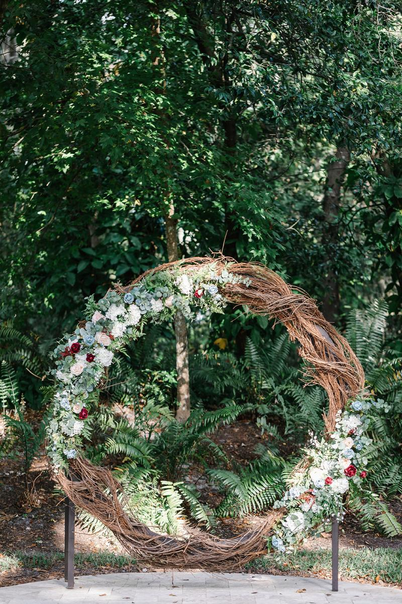 The grape vine wreath decorated with dusty blue and burgundy flowers