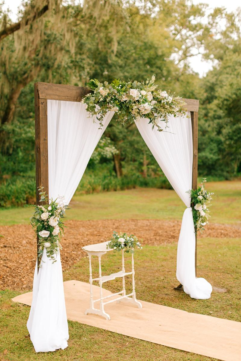Wooden arch with white draping for this oak tree wedding